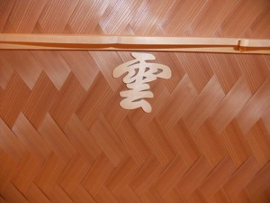 "The character for ""clouds"", in wood, stuck to the ceiling over the kamidana."