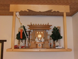 The kamidana with the offerings added in the front centre, in front of the miyagata