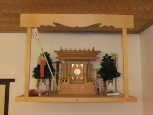 The sakaki have now been added to the kamidana, in front of the o-fuda but behind the hamaya