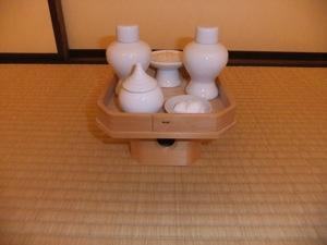 Five ceramic vessels on a wooden platform