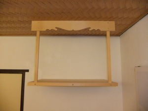 A wooden shelf, high on the wall, with a wooden beam above it.