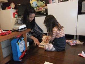 真由喜がプレゼントに囲まれ、ゆり子と一緒に絵本を読む