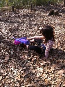 真由喜が落ち葉の中に座って、自分を埋めようとする