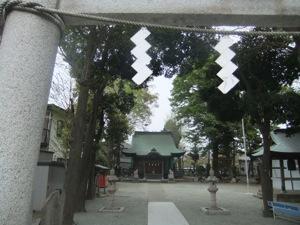 金属の紙垂が見える鳥居から社殿を見る