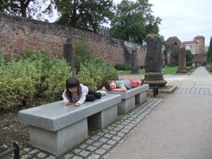 真由喜とお友達がローマ時代の柱のまえに新しい意志のベンチにうつぶせになる。背景二は、チェスターの中世の塀が見える。
