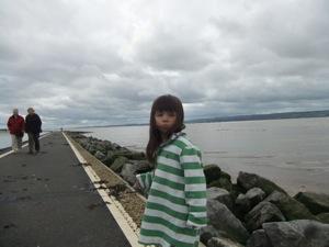 大きなセーターを着た真由喜が灰色の空の下で茶色の海の前に立つ