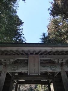 神社の門を見上げて、木と青空が見える