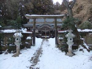雪の中で、鳥居の無効に社殿が見える。