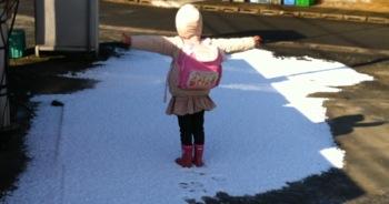 真由喜が雪の端で立って、腕を広げる