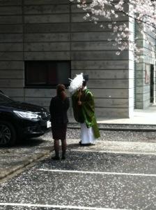 桜の下で神職が車を祓う