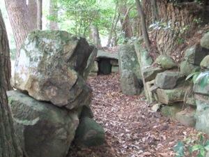 土や天井がなくなった古墳で、石の壁が見える。