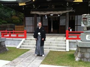 私が紋付羽織袴で白幡八幡大神の社殿の前に立つ