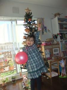 真由喜がクリスマスツリーの前で立って、ほぼ隠す