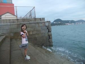 海に降りる階段に立つ真由喜