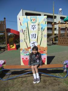真由喜が卒園式と書いてある看板の前に座っている。
