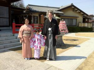 私、ゆり子と真由喜が神社の境内で和装で立つ