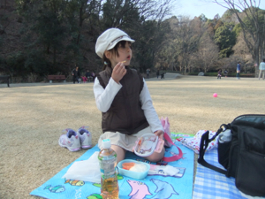 真由喜が公園の芝生で弁当を食べる