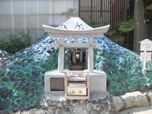小さな石鳥居の後ろに、彩られた富士山の模型が立つ。その中のアナには、神鏡が見える。
