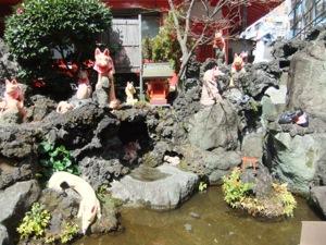 人工池の周りの岩に狐像が群れる。