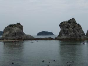 大きな岩の間に向こうにある島が浮かぶ