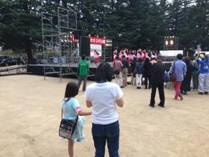 公園で、ゆり子と真由喜が舞台の上の踊りを観賞する