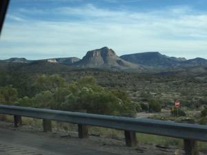 車の窓から低木がある砂漠の奥には、風邪などに削られた山が見える